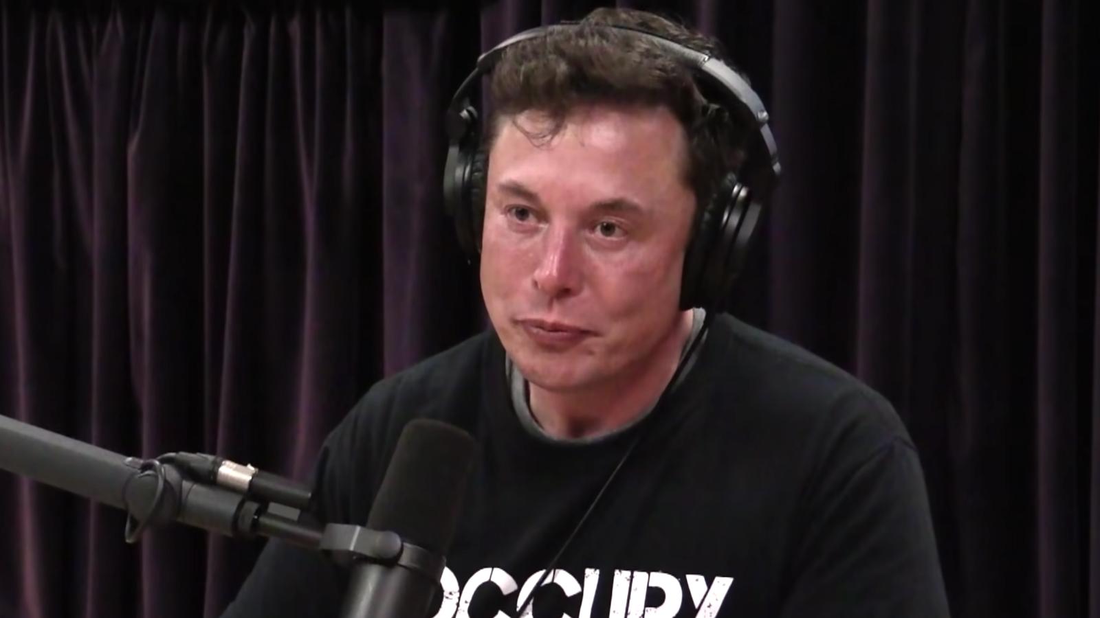 Elon Musk sitting on Joe Rogan's podcast in black t-shirt with headphones on.