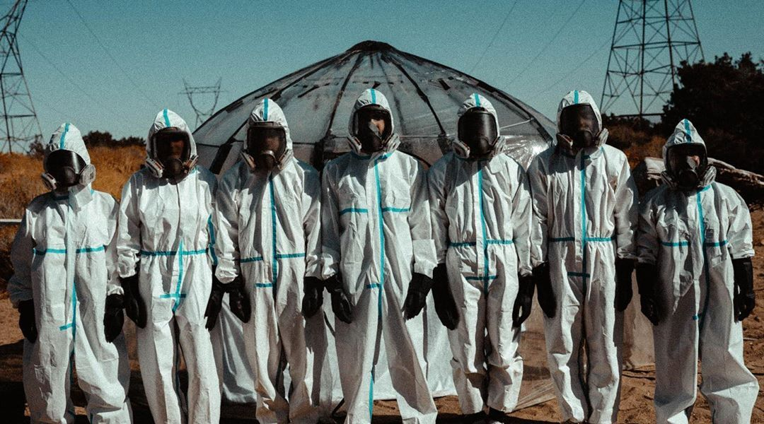 The Lab content house stand together, dressed in hazmat suits to hide their face.