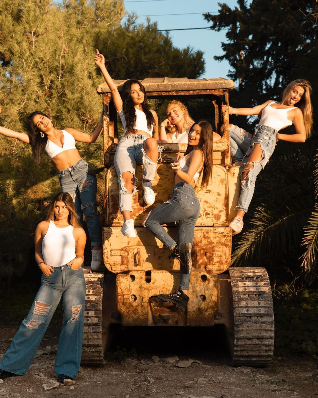 Clubhouse Europe household members posing on an old, dilapidated tractor